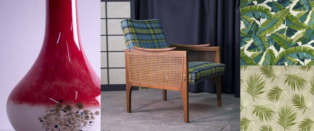 Red art glass vase. Mid Century modern rattan lounge chair. Tropical fabric samples.